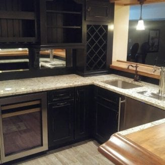 Porcelain floor installation with black rusted cabinets and wood with granite top bar combination in Baltimore