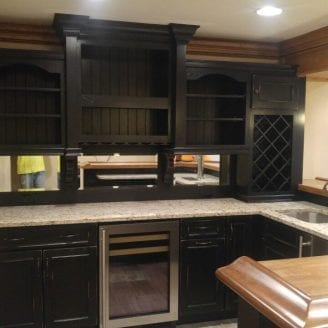 basement-bar-installation-with-black-rusted-look-cabinets