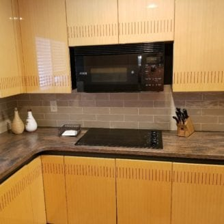 Corian counter top with cooktop and tile backsplash